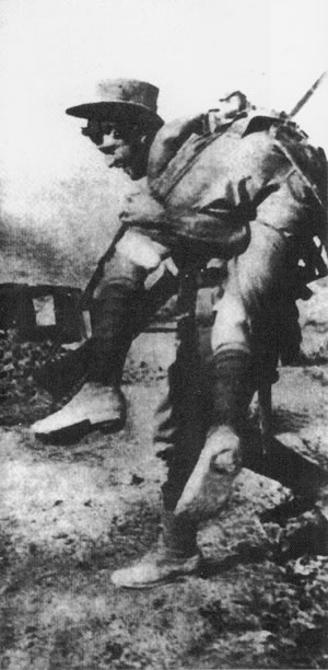 Photograph of a man carry another man through battle